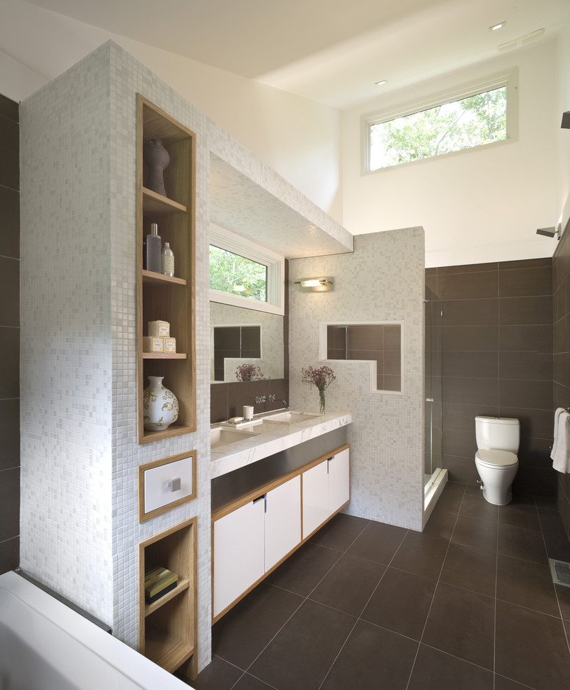 Large trendy master brown tile and stone tile limestone floor alcove shower photo in New York with an undermount sink, flat-panel cabinets, white cabinets, a two-piece toilet, marble countertops and brown walls