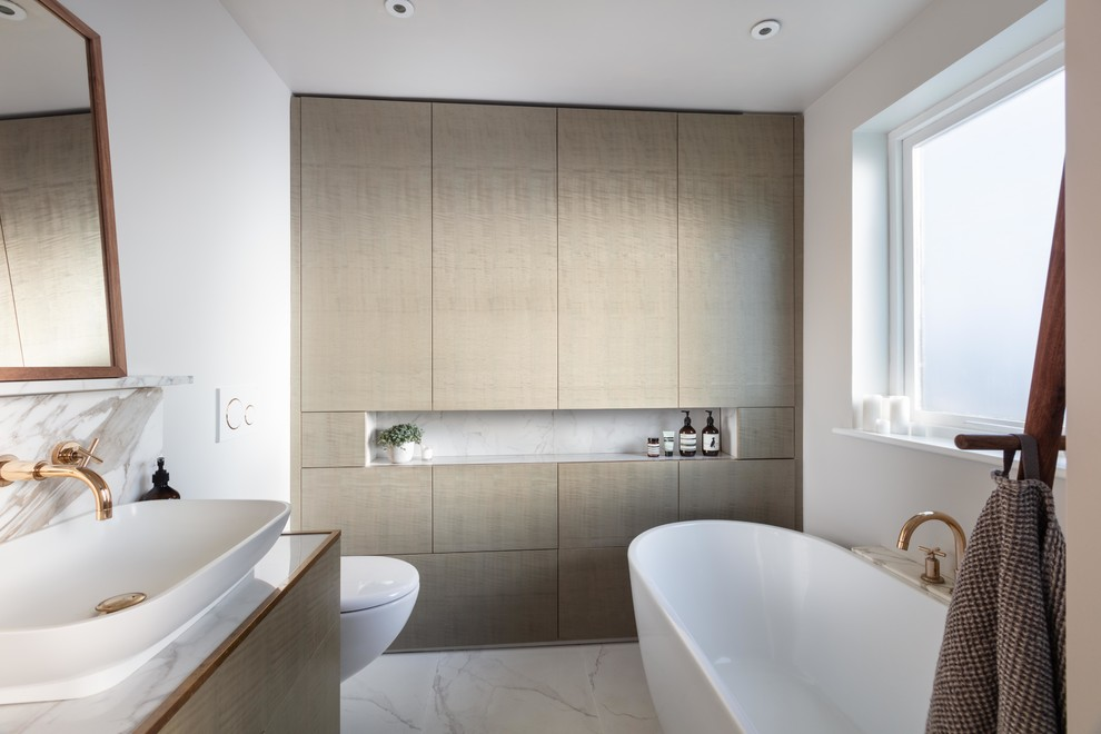 Small trendy kids' ceramic tile and gray floor freestanding bathtub photo in London with flat-panel cabinets, gray cabinets, a wall-mount toilet, marble countertops, gray countertops, white walls and a vessel sink