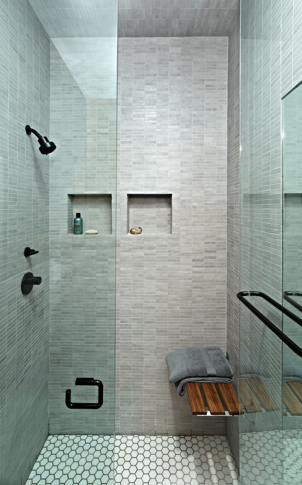 Trendy gray tile and mosaic tile shower bench photo in New York with a niche