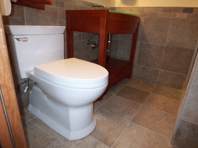 Easy to clean concealed trapway Toto toilet with stylish and cohesive tile on fl