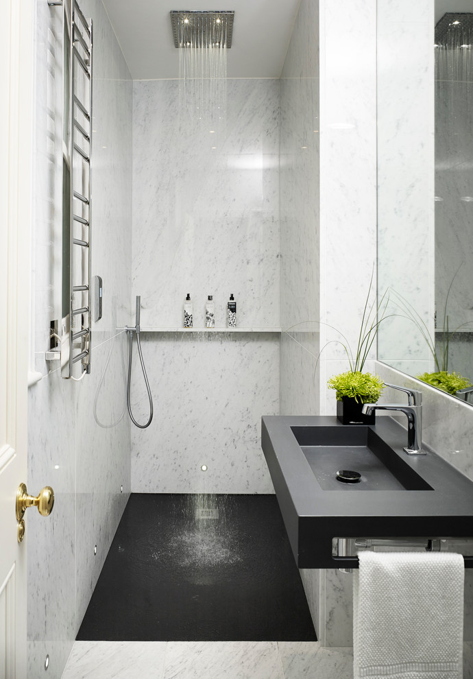 Trendy white tile and stone tile marble floor and gray floor walk-in shower photo in London with an integrated sink and white walls