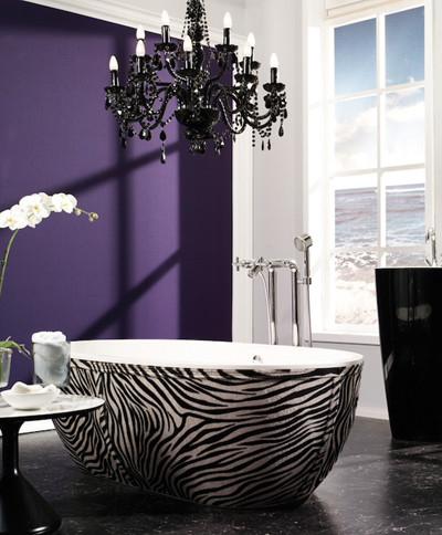 A Gothic-inspired bathroom featuring a black crystal chandelier, a purple accent wall and an animal-printed bath tub