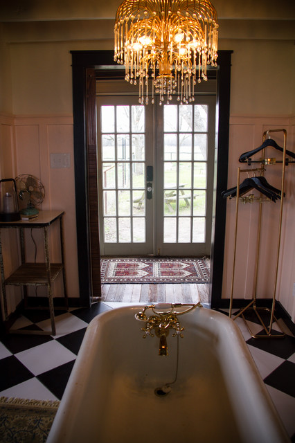 Bathroom - large country master black and white tile and ceramic tile ceramic floor and black floor bathroom idea in Austin with furniture-like cabinets, a one-piece toilet, pink walls, a vessel sink, wood countertops and brown countertops