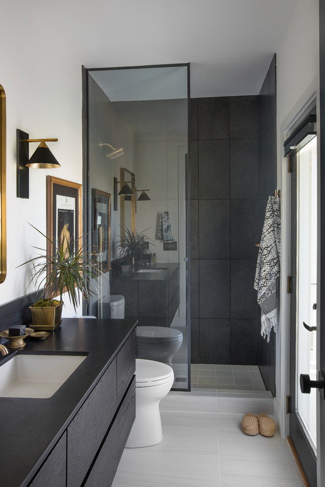 Trendy white tile white floor bathroom photo in Charleston with an undermount sink, flat-panel cabinets, black cabinets, white walls and black countertops