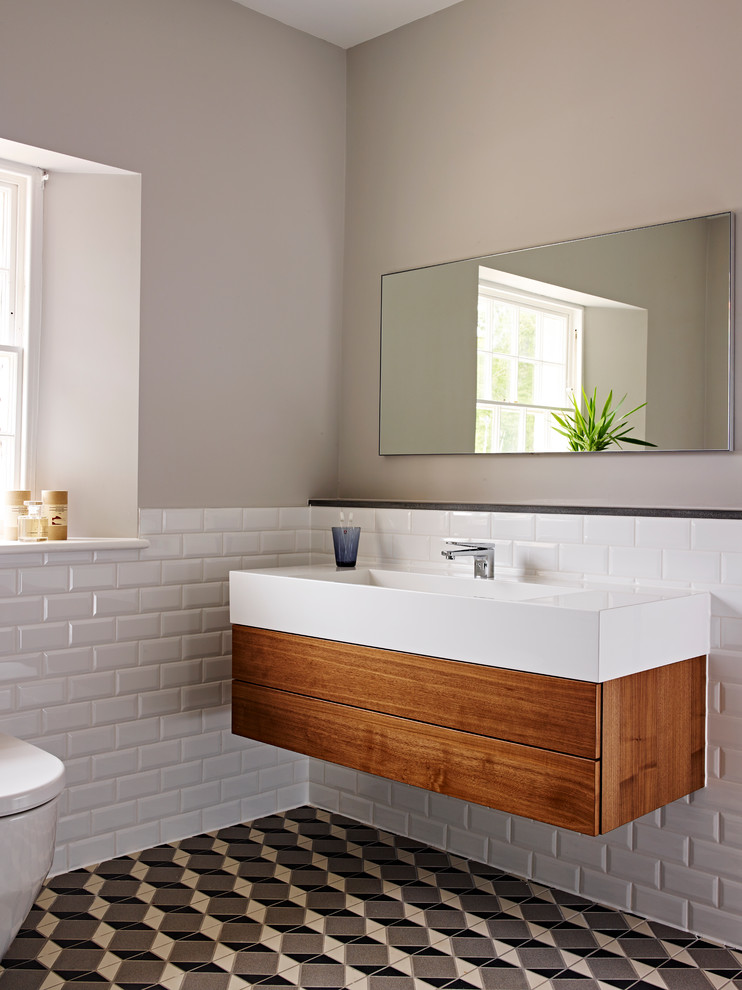 Inspiration for a mid-sized timeless white tile ceramic tile bathroom remodel in Devon with a wall-mount sink, flat-panel cabinets, medium tone wood cabinets and a one-piece toilet