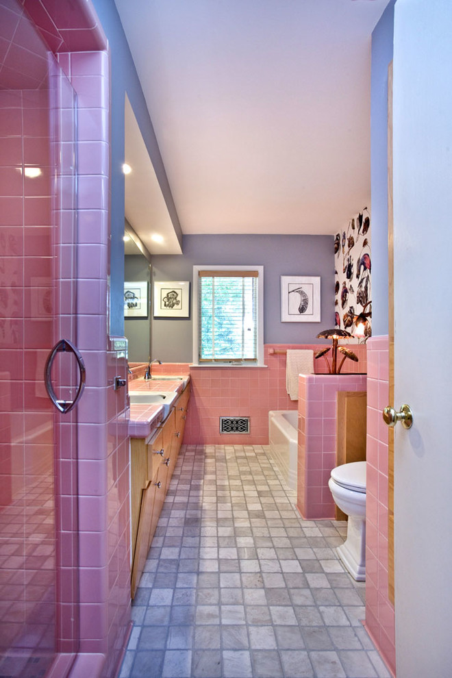 Example of an eclectic pink tile porcelain tile bathroom design in Minneapolis with flat-panel cabinets, light wood cabinets, a two-piece toilet, gray walls, an integrated sink and tile countertops