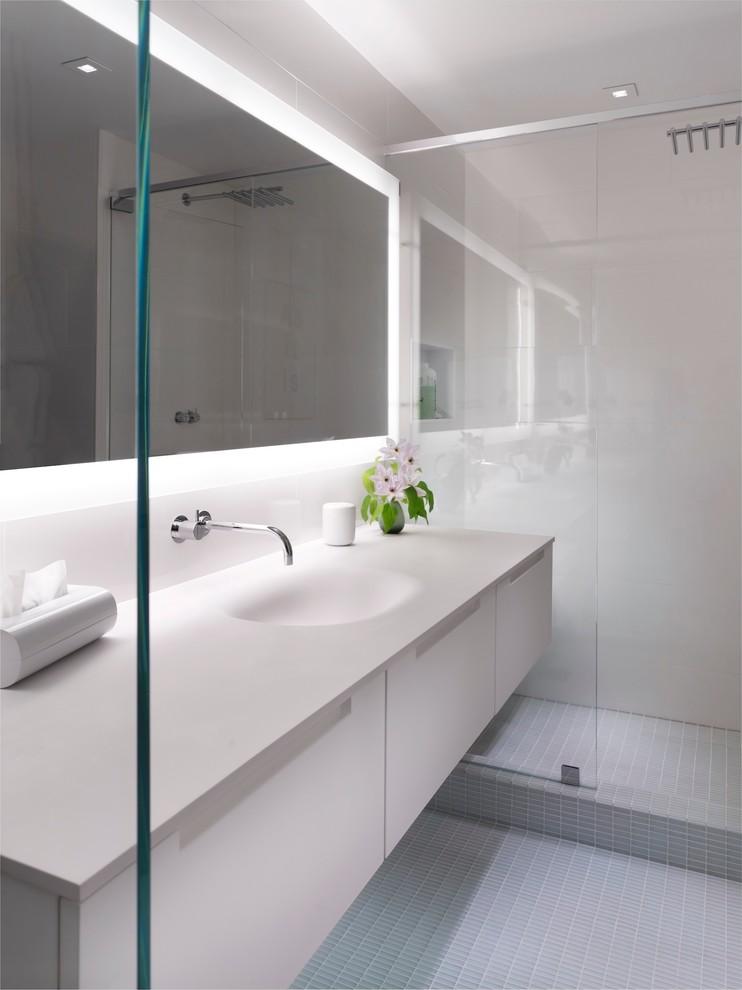 Ispirazione per una grande stanza da bagno padronale design con lavabo integrato, ante lisce, ante bianche, doccia alcova, pavimento con piastrelle a mosaico, top in superficie solida, piastrelle grigie, piastrelle in ceramica, pareti bianche, pavimento grigio e top bianco