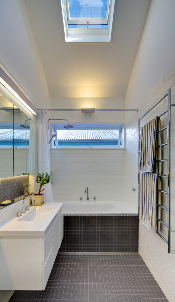 Bathroom - mid-sized contemporary master gray tile and ceramic tile mosaic tile floor bathroom idea in Sydney with an integrated sink, flat-panel cabinets, white cabinets, solid surface countertops and white walls