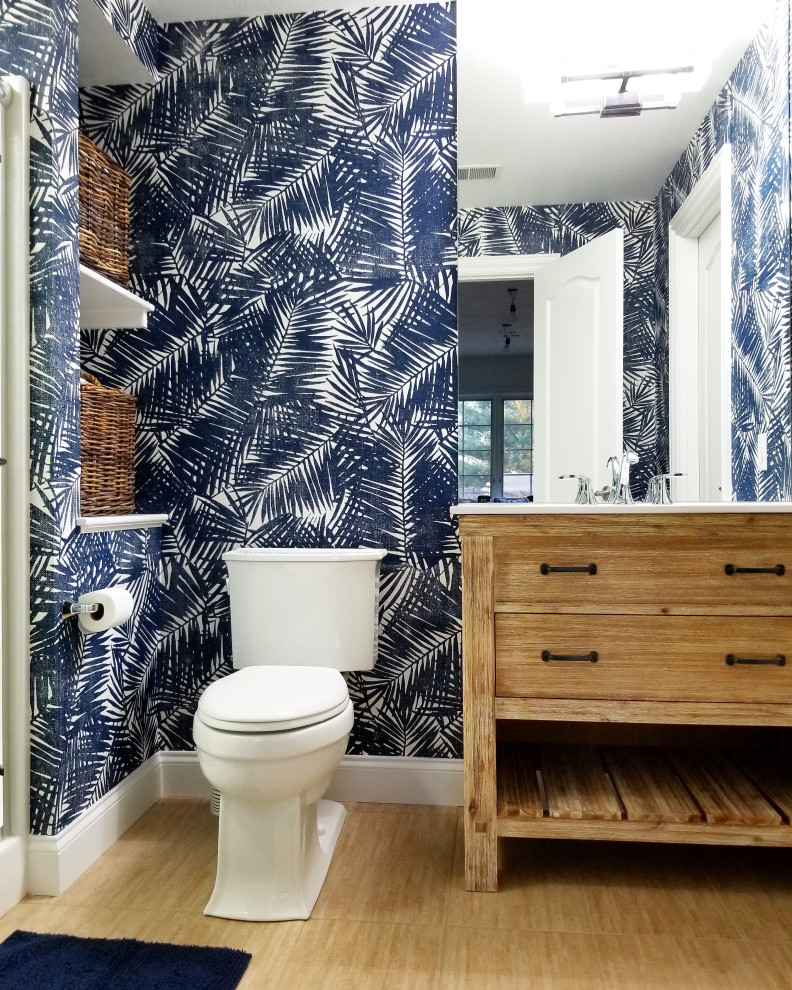 Inspiration for a tropical 3/4 medium tone wood floor and brown floor alcove shower remodel in Philadelphia with flat-panel cabinets, medium tone wood cabinets, a two-piece toilet, multicolored walls, an undermount sink and white countertops