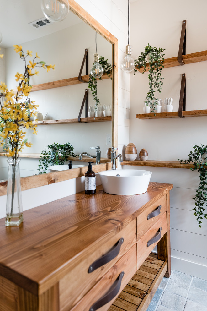 Inspiration for a country gray floor bathroom remodel in Sacramento with furniture-like cabinets, medium tone wood cabinets, white walls, a vessel sink, wood countertops and brown countertops