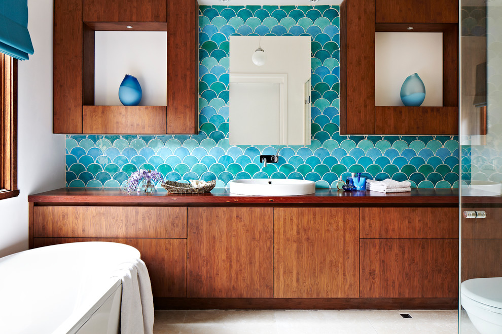 Design ideas for a contemporary master bathroom in Melbourne with a vessel sink, flat-panel cabinets, medium wood cabinets, wood benchtops, a freestanding tub, blue tile, blue walls and brown benchtops.