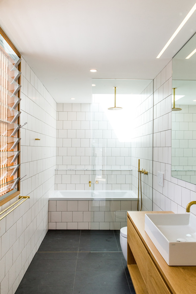 Contemporary master bathroom in Sydney with flat-panel cabinets, medium wood cabinets, an alcove tub, a curbless shower, a one-piece toilet, white tile, white walls, a vessel sink, wood benchtops, black floor and concrete floors.