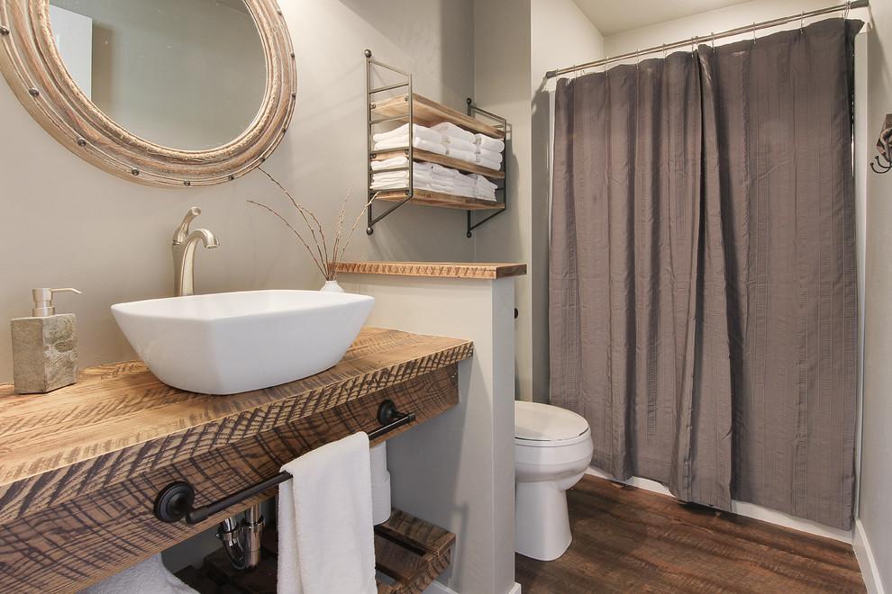 Ejemplo de cuarto de baño de estilo de casa de campo con ducha empotrada, paredes grises, suelo de madera oscura, lavabo sobreencimera, encimera de madera, suelo marrón, ducha con cortina y encimeras marrones