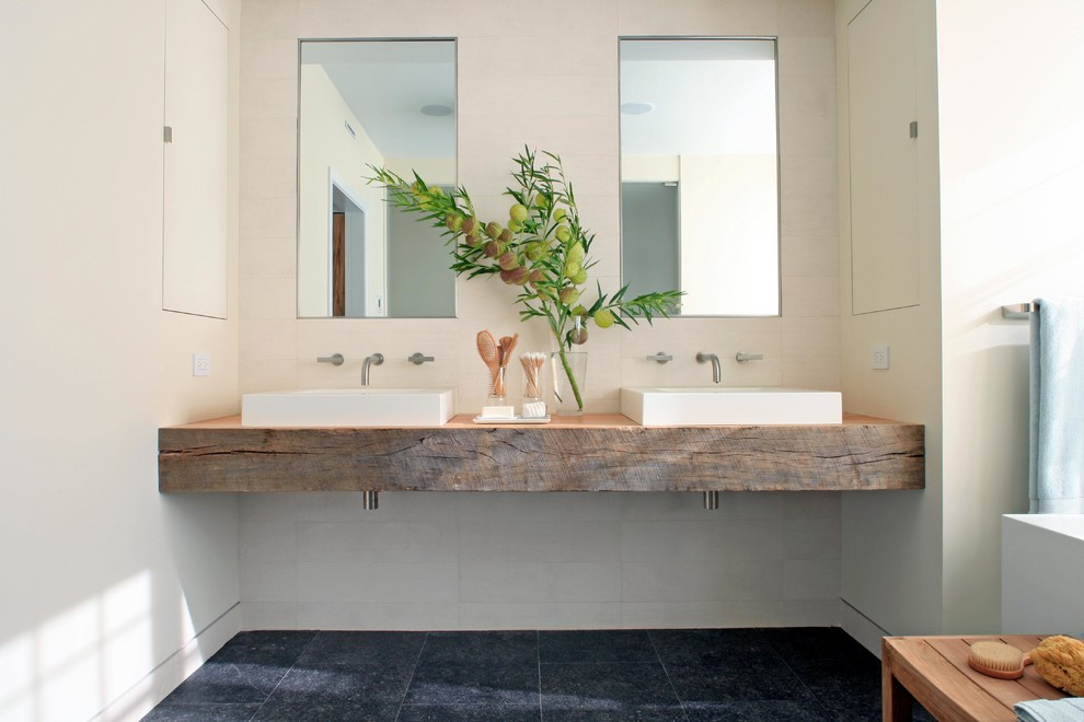 Mid-sized trendy master white tile and porcelain tile porcelain floor and black floor bathroom photo in Chicago with a vessel sink, open cabinets, medium tone wood cabinets, white walls, wood countertops and brown countertops