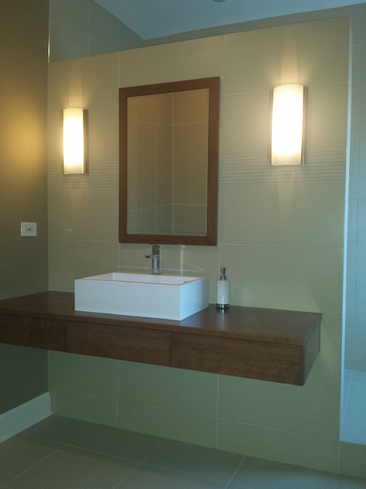 Example of a mid-sized trendy master ceramic tile ceramic tile bathroom design in Chicago with a vessel sink, flat-panel cabinets, dark wood cabinets and wood countertops
