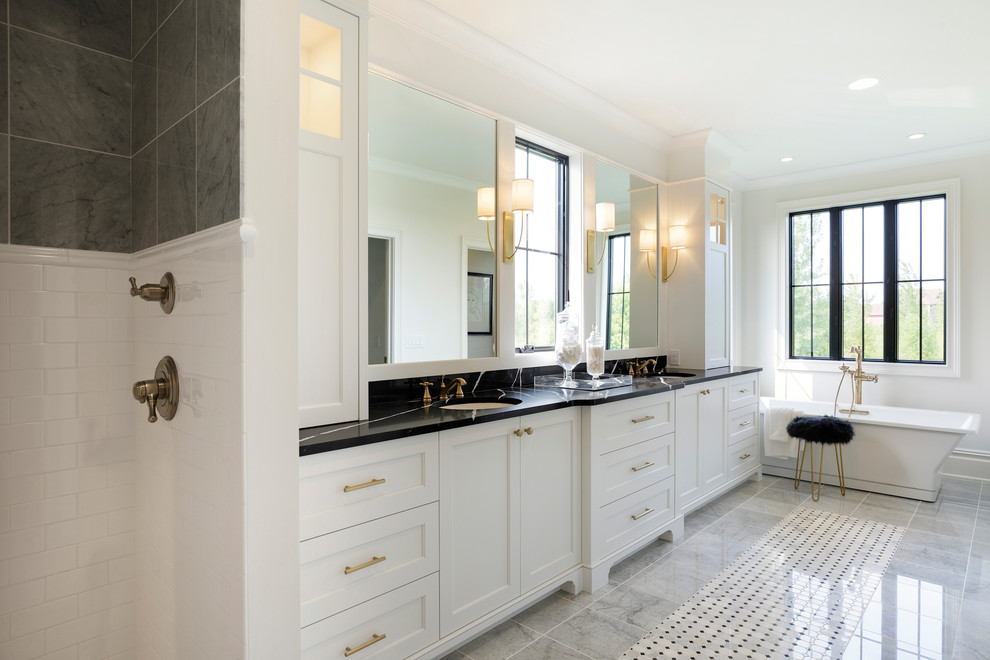 Elegant master gray tile multicolored floor freestanding bathtub photo in Minneapolis with shaker cabinets, white cabinets, white walls and an undermount sink