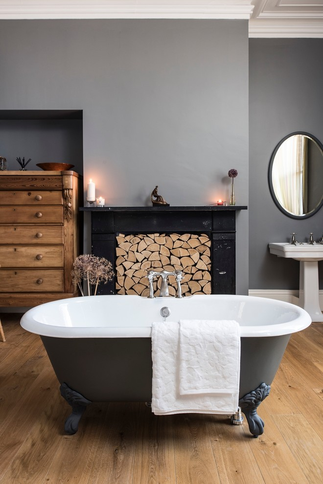 Inspiration for a large timeless master medium tone wood floor claw-foot bathtub remodel in London with a pedestal sink and gray walls