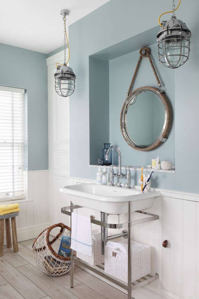 Small beach style master light wood floor bathroom photo in London with blue walls and a console sink