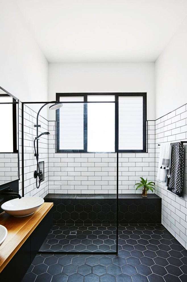 Example of a mid-sized urban 3/4 white tile and subway tile ceramic tile and black floor bathroom design in Other with black cabinets, white walls, a vessel sink, wood countertops and brown countertops
