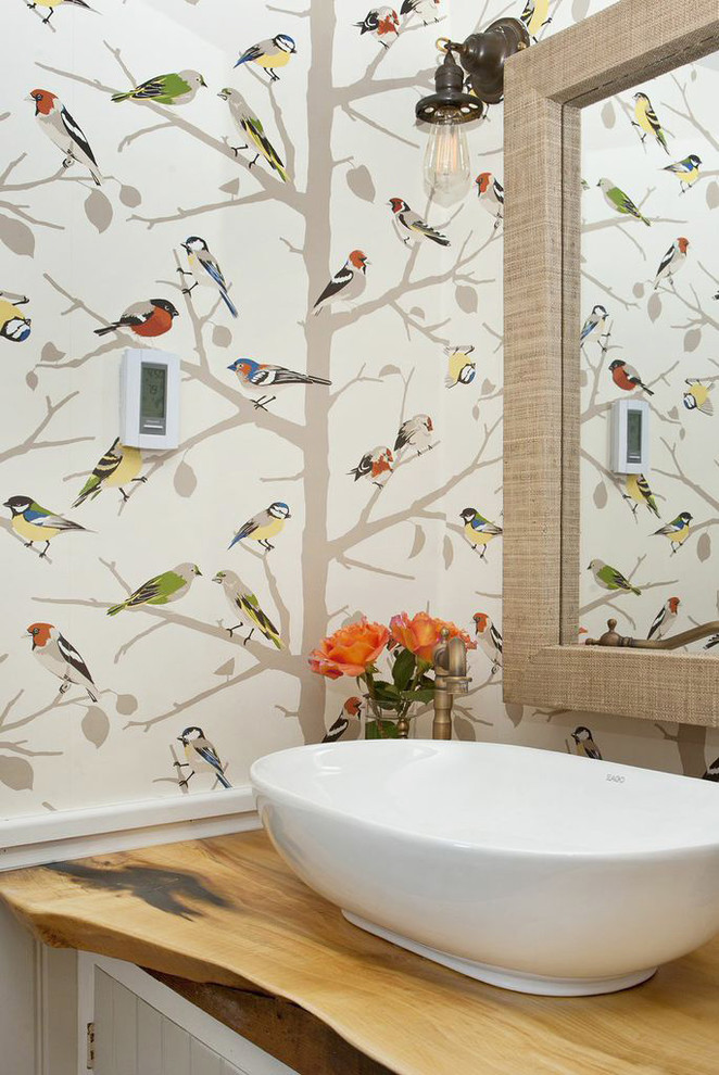 Example of a country bathroom design in New York with a vessel sink, wood countertops and multicolored walls