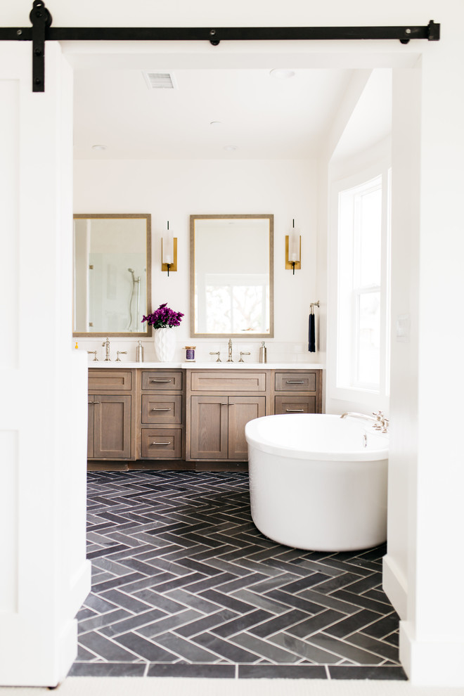 Large farmhouse master porcelain floor and black floor freestanding bathtub photo in San Diego with shaker cabinets, dark wood cabinets, white walls, an undermount sink and quartz countertops