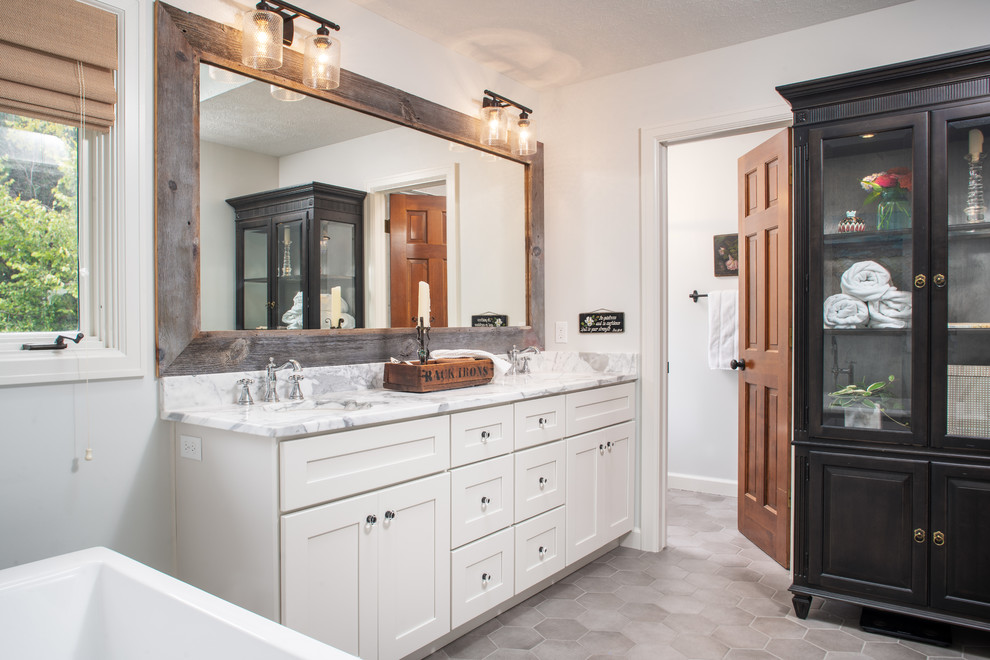 Freestanding bathtub - mid-sized cottage master porcelain tile and gray floor freestanding bathtub idea in Omaha with shaker cabinets, white cabinets, white walls, an undermount sink, marble countertops and white countertops