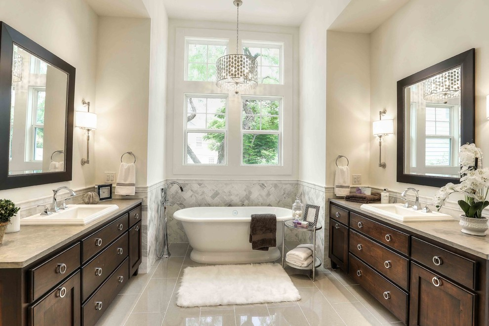 Example of a classic gray tile freestanding bathtub design in Austin with dark wood cabinets, white walls, a drop-in sink and shaker cabinets
