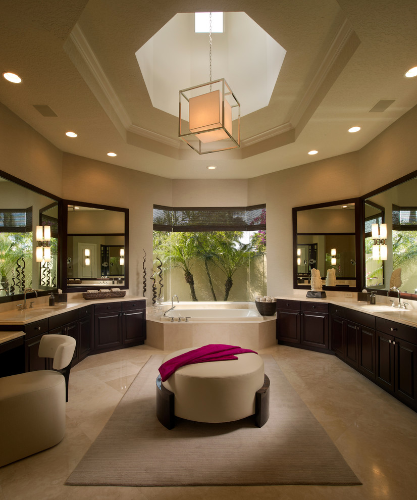 Example of a trendy beige tile beige floor drop-in bathtub design in Miami with an undermount sink, raised-panel cabinets and dark wood cabinets