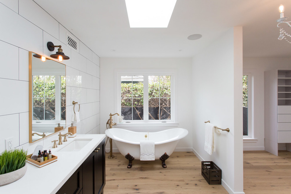 Example of a farmhouse master white tile claw-foot bathtub design in Los Angeles with shaker cabinets and black cabinets