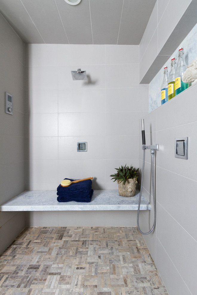 Trendy master gray tile and porcelain tile porcelain tile bathroom photo in Minneapolis with an undermount sink, flat-panel cabinets, medium tone wood cabinets, onyx countertops, a one-piece toilet and gray walls