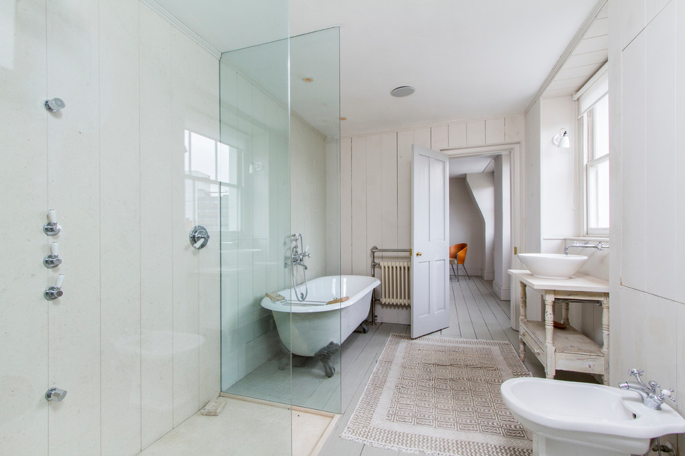Example of an ornate claw-foot bathtub design in London with a bidet and a vessel sink