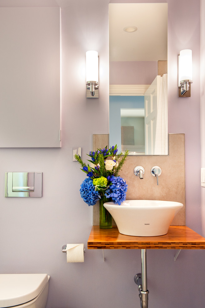 Example of a trendy bathroom design in Boston with a vessel sink, wood countertops, a wall-mount toilet, purple walls and brown countertops