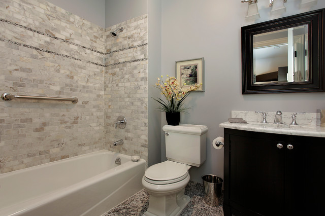 Elegant gray tile and stone tile bathroom photo in Denver with raised-panel cabinets, dark wood cabinets, marble countertops, a two-piece toilet and gray walls