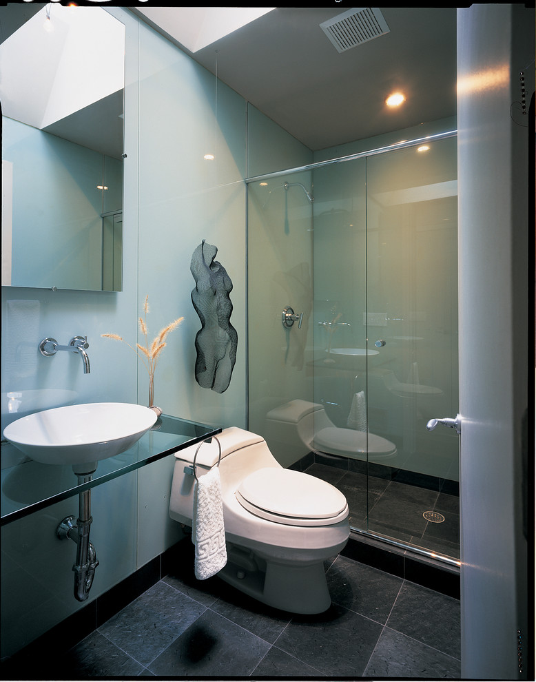 Example of a minimalist gray tile alcove shower design in DC Metro with a vessel sink and glass countertops