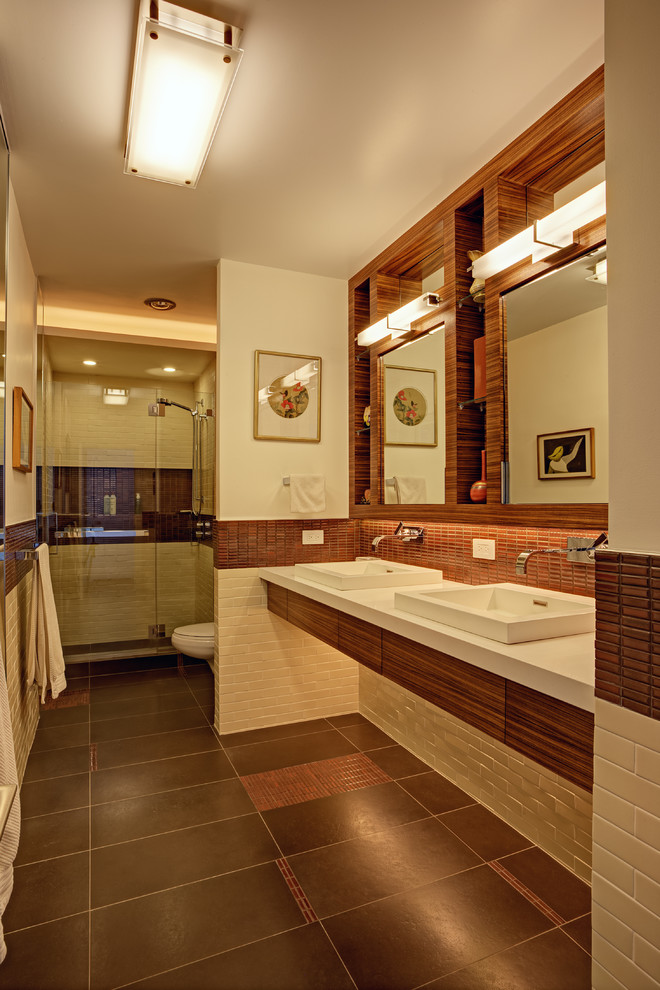 Mid-sized trendy master beige tile and subway tile porcelain tile and brown floor doorless shower photo in San Francisco with a drop-in sink, flat-panel cabinets, medium tone wood cabinets, solid surface countertops, white walls, a hinged shower door and a wall-mount toilet