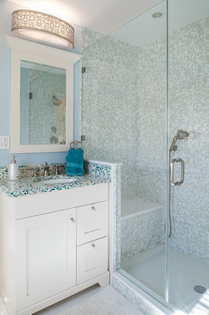 Example of a mid-sized classic 3/4 multicolored tile and mosaic tile white floor alcove shower design in New York with an undermount sink, shaker cabinets, white cabinets, blue walls, blue countertops, recycled glass countertops and a hinged shower door