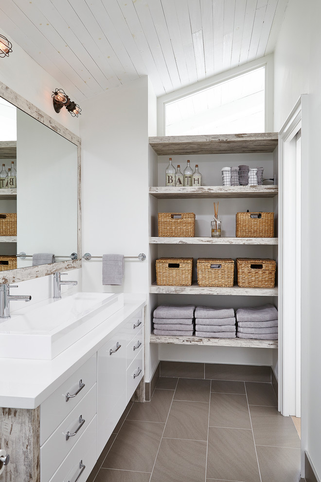 Mid-sized transitional 3/4 beige tile porcelain tile bathroom photo in Toronto with flat-panel cabinets, a two-piece toilet, white walls, a trough sink, white cabinets, solid surface countertops and white countertops