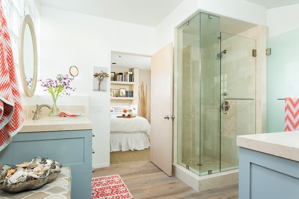 Large beach style kids' beige tile and marble tile light wood floor and gray floor alcove shower photo in Los Angeles with shaker cabinets, blue cabinets, a one-piece toilet, white walls, an undermount sink, marble countertops and a hinged shower door