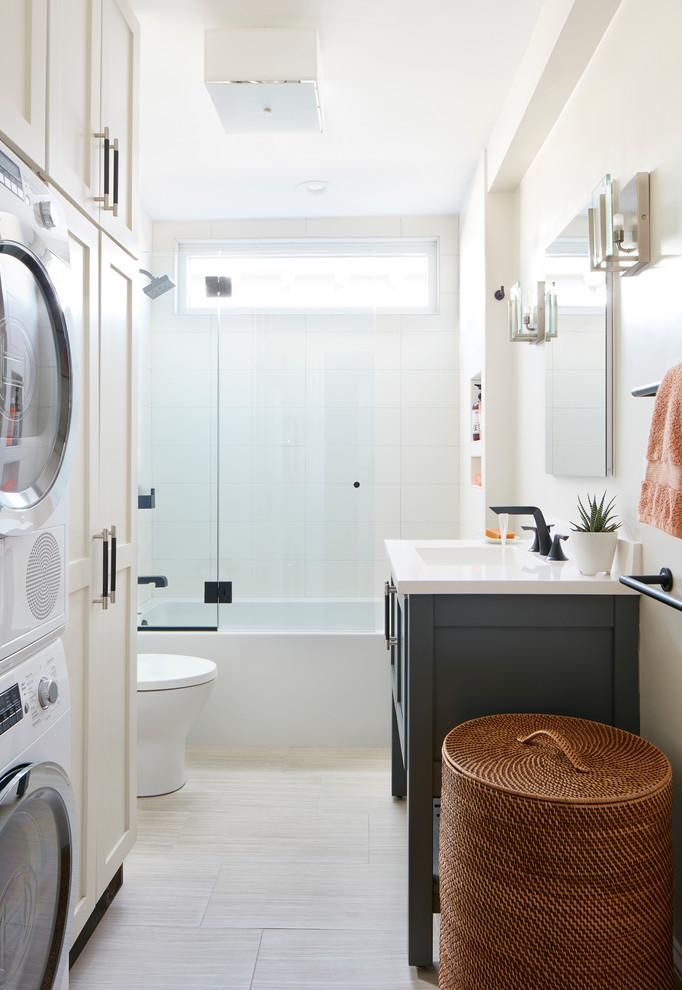 Modelo de cuarto de baño principal, contemporáneo, pequeño, con armarios estilo shaker, puertas de armario blancas, bañera encastrada, combinación de ducha y bañera, sanitario de dos piezas, baldosas y/o azulejos beige, baldosas y/o azulejos de porcelana, paredes blancas, suelo de baldosas de porcelana, lavabo tipo consola, suelo beige y tendedero