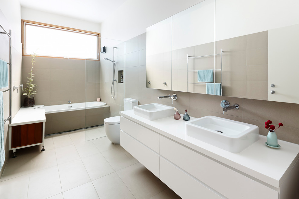This is an example of a contemporary bathroom in Melbourne with a drop-in tub, an open shower, ceramic floors, grey walls, gray tile, a drop-in sink, flat-panel cabinets, white cabinets and an open shower.