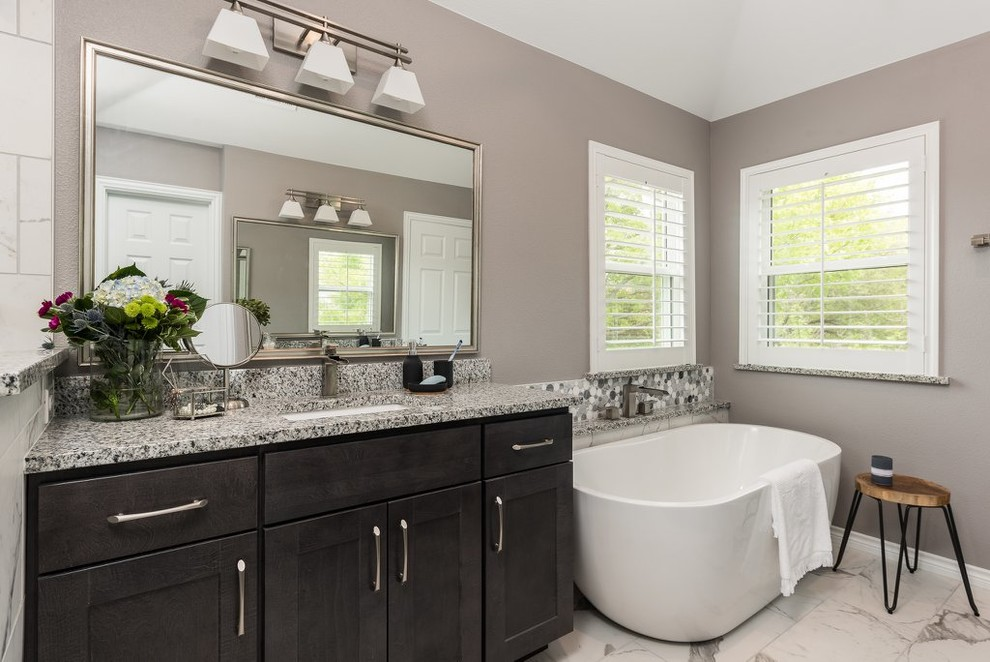 Inspiration for a large transitional master multicolored tile and marble tile marble floor and multicolored floor bathroom remodel in Dallas with shaker cabinets, dark wood cabinets, a one-piece toilet, gray walls, an undermount sink, granite countertops, a hinged shower door and multicolored countertops