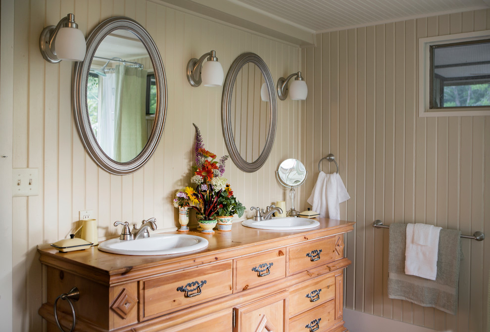Bathroom - cottage bathroom idea in St Louis with a drop-in sink, furniture-like cabinets, beige walls and medium tone wood cabinets
