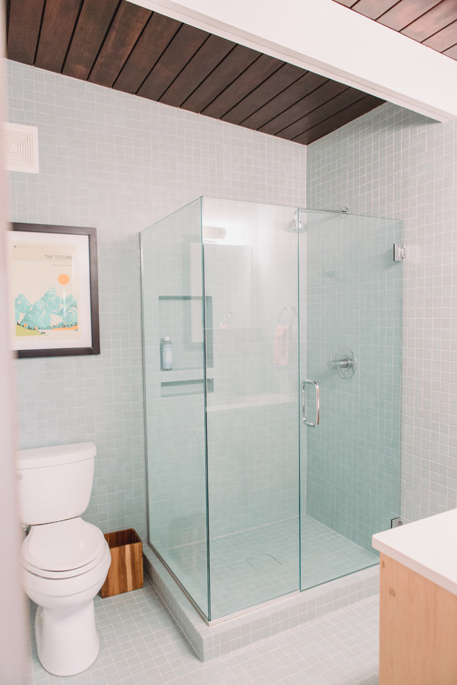 Small 1960s master blue tile and ceramic tile ceramic floor and blue floor corner shower photo in Grand Rapids with flat-panel cabinets, light wood cabinets, a two-piece toilet, white walls, an integrated sink, quartz countertops, a hinged shower door and white countertops