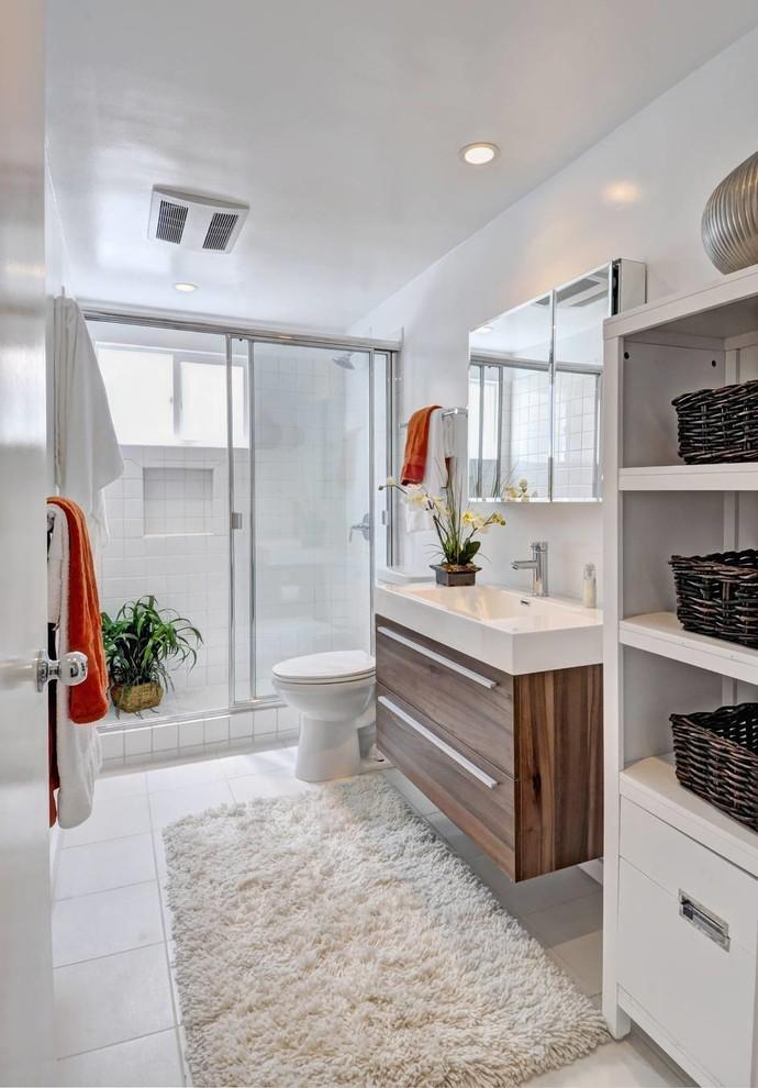 ロサンゼルスのコンテンポラリースタイルのおしゃれな浴室 (一体型シンク、フラットパネル扉のキャビネット、中間色木目調キャビネット、アルコーブ型シャワー) の写真