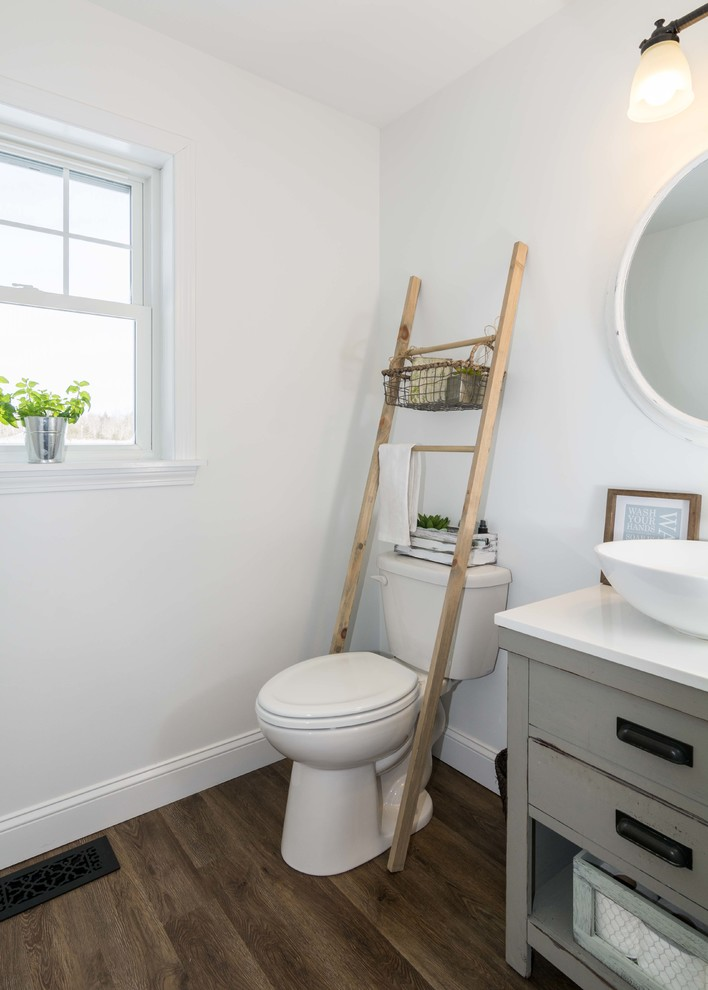 Small farmhouse 3/4 vinyl floor and brown floor bathroom photo in Portland Maine with furniture-like cabinets, gray cabinets, white walls, a vessel sink, a two-piece toilet and solid surface countertops