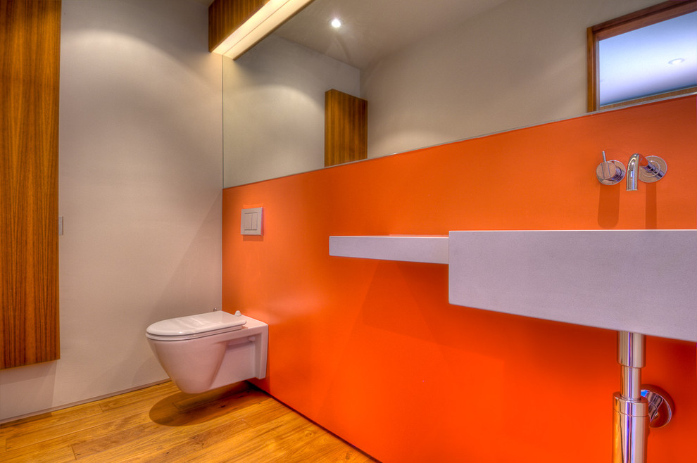 Inspiration for a modern bathroom remodel in Los Angeles with a wall-mount sink, a wall-mount toilet and orange walls