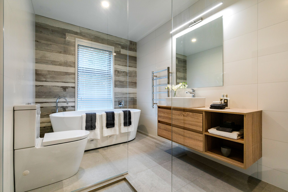 Bathroom - contemporary master beige tile gray floor bathroom idea in Auckland with flat-panel cabinets, medium tone wood cabinets, a one-piece toilet, beige walls, a vessel sink and wood countertops