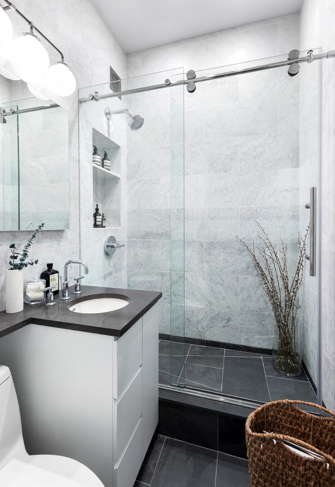 Example of a small trendy 3/4 white tile and marble tile black floor bathroom design in New York with flat-panel cabinets, white cabinets, a one-piece toilet and an undermount sink