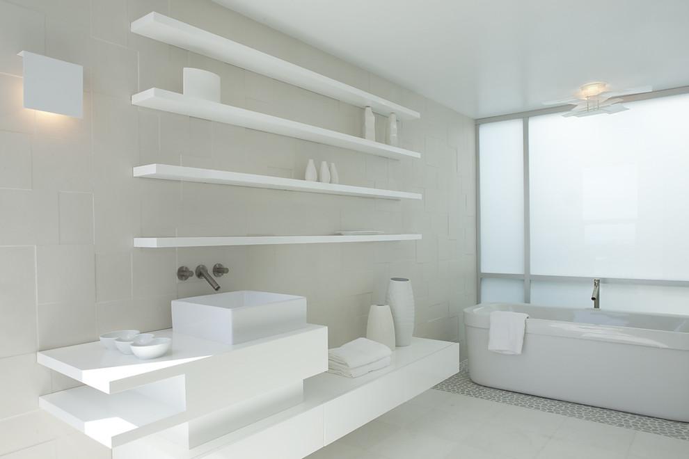 Freestanding bathtub - modern pebble tile floor freestanding bathtub idea in San Francisco with a vessel sink