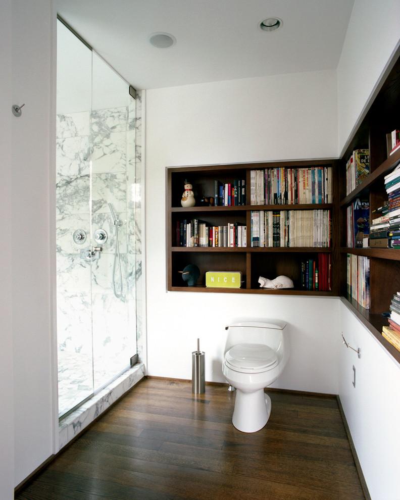 Modelo de cuarto de baño principal, actual, grande, con sanitario de una pieza, paredes blancas, suelo de madera oscura, armarios abiertos, puertas de armario de madera en tonos medios, ducha empotrada y losas de piedra